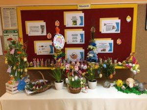 Stół wielkanocny ozdobiony potrawami oraz pięknymi ozdobami. Za stołem widnieją prace wielkanocne wykonane przez dzieci z naszego przedszkola. Na tablicy za stołem wywieszone są ważne informacje dotyczące świąt Wielkanocnych.